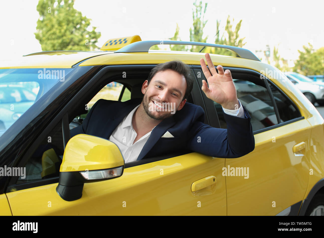 Male taxi driver sitting in yellow car - Stock Image