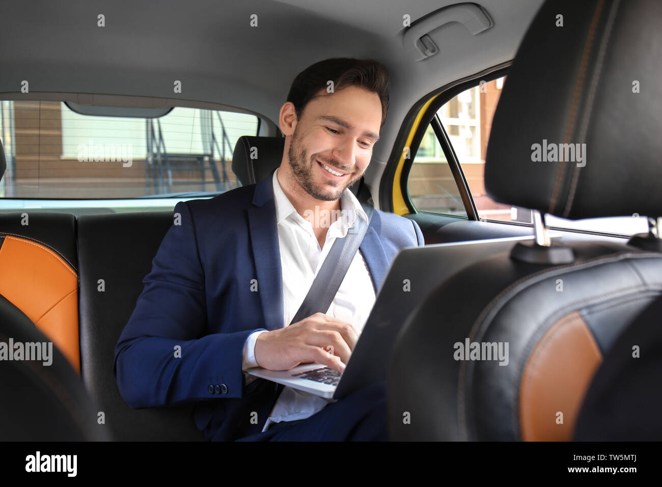 Handsome man with laptop sitting in taxi car - Stock Image
