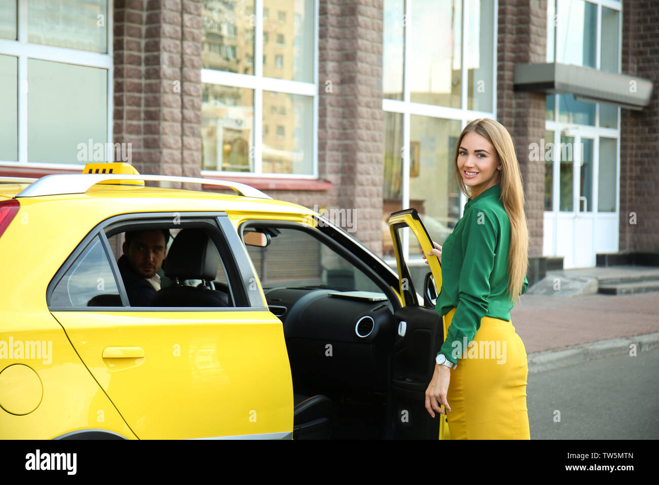 Young woman standing near taxi car on street - Stock Image