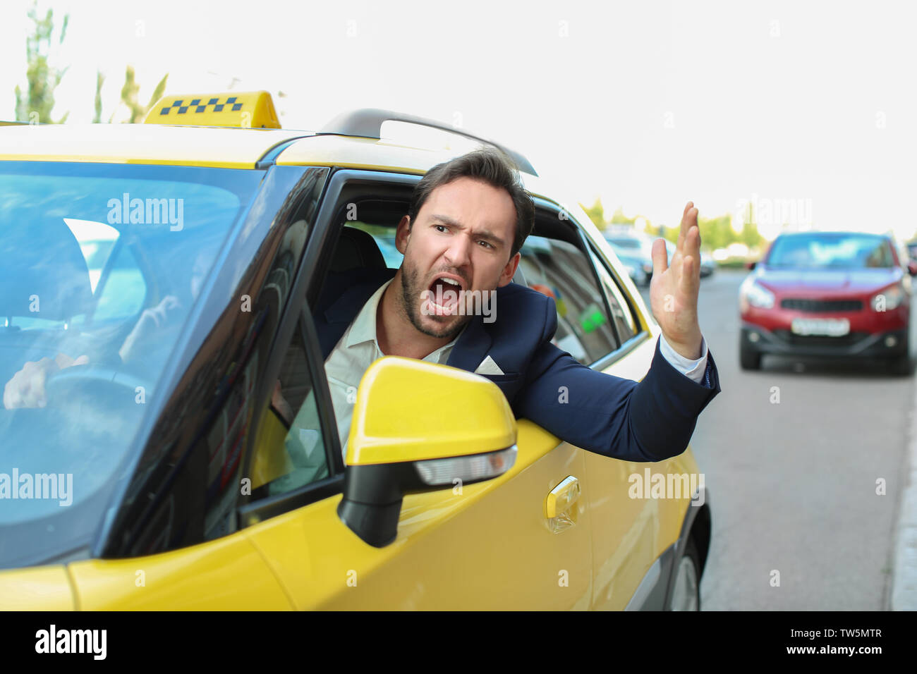 Emotional male taxi driver sitting in yellow car - Stock Image