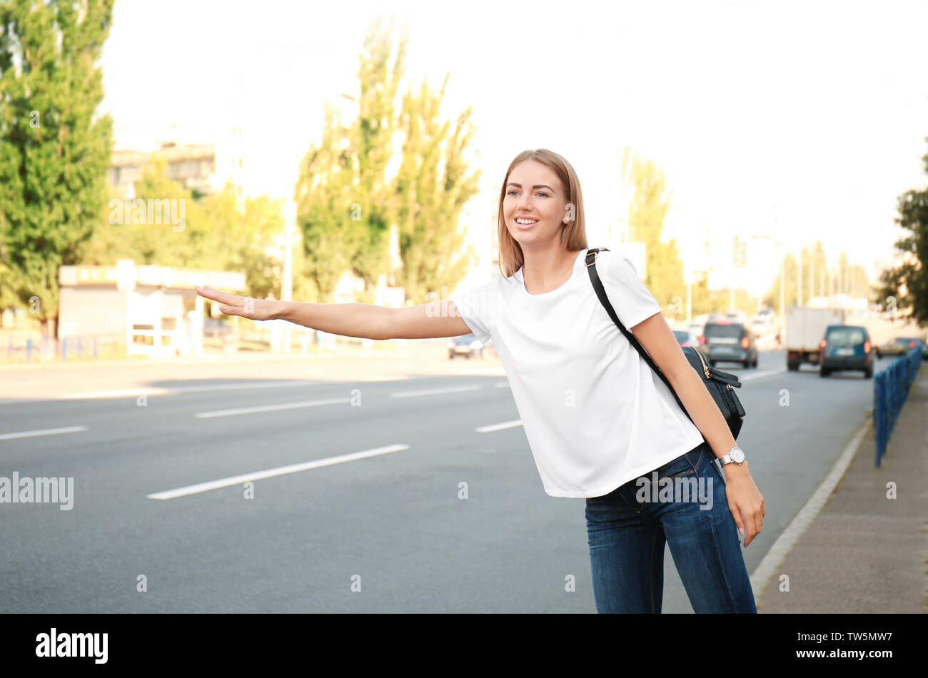 Young woman catching taxi on street - Stock Image