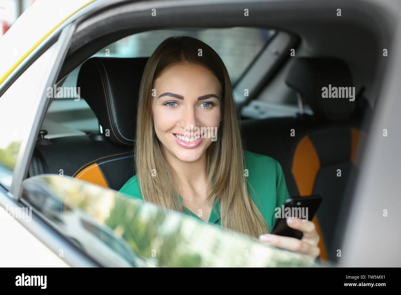 Beautiful woman with phone sitting in taxi - Stock Image