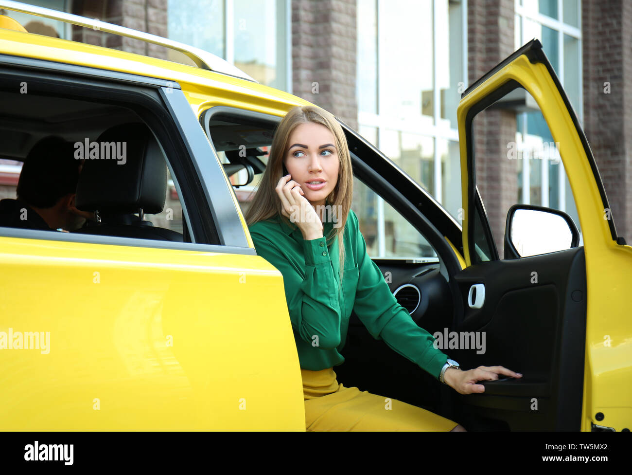 Young woman talking on phone in taxi car - Stock Image