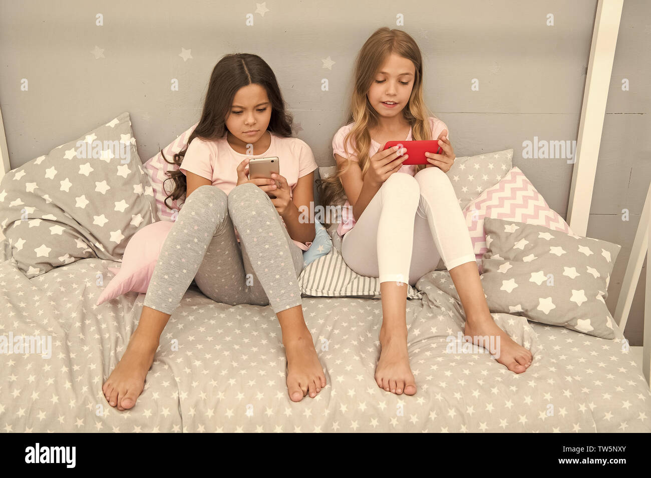 Smartphone for entertainment. Kids taking selfie. Smartphone application concept. Girlish leisure pajama party. Girls smartphone little bloggers. Onli - Stock Image