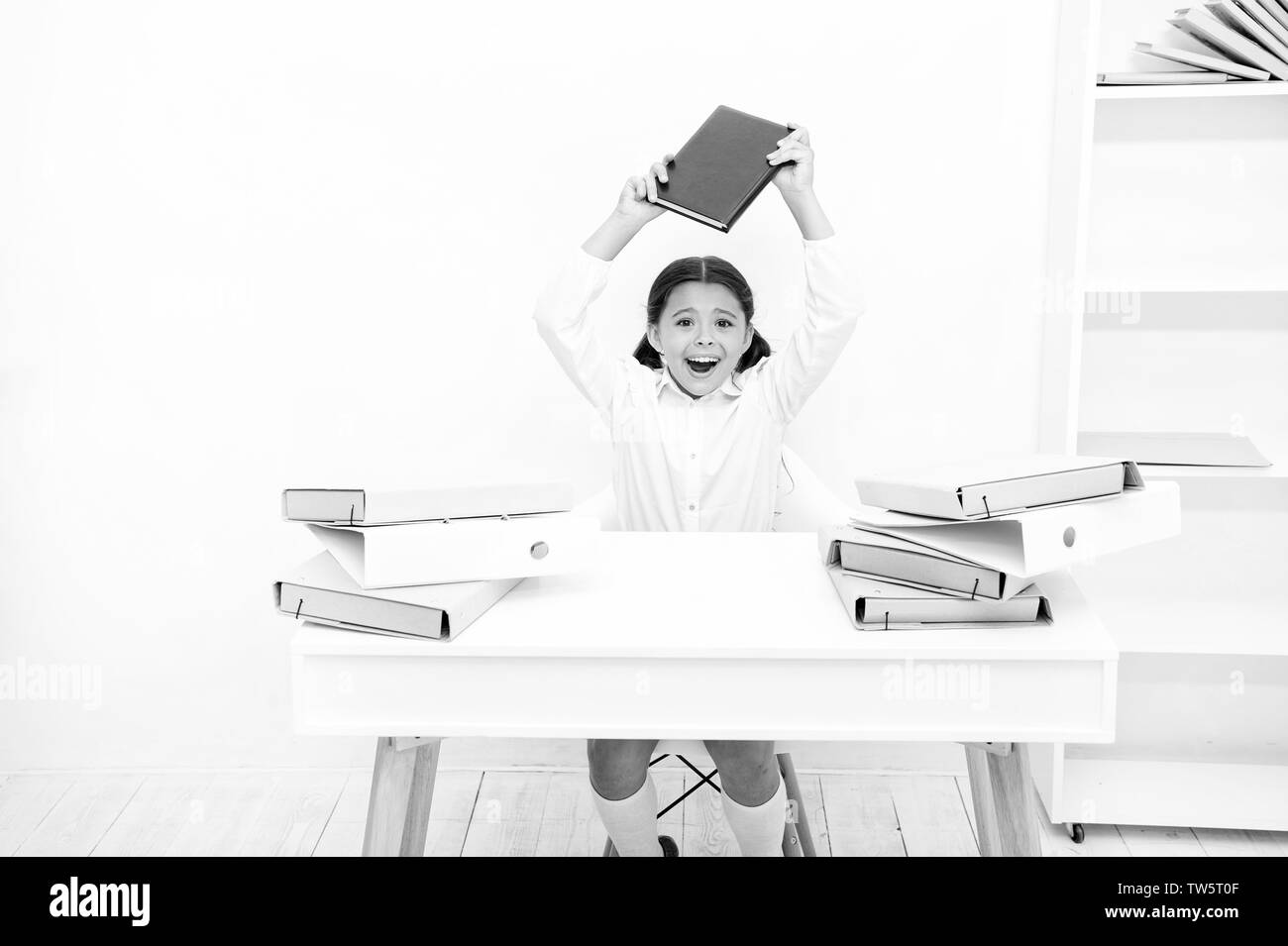 In capricious mood. Naughty child being noisy at school. Little child refusing to learn literacy. Small girl raising book over head. Angry girl hates - Stock Image