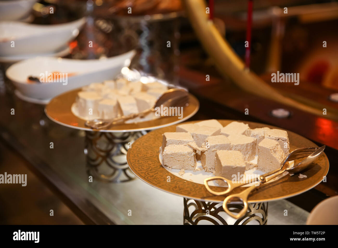 Plates with different kinds of desserts on table at buffet - Stock Image