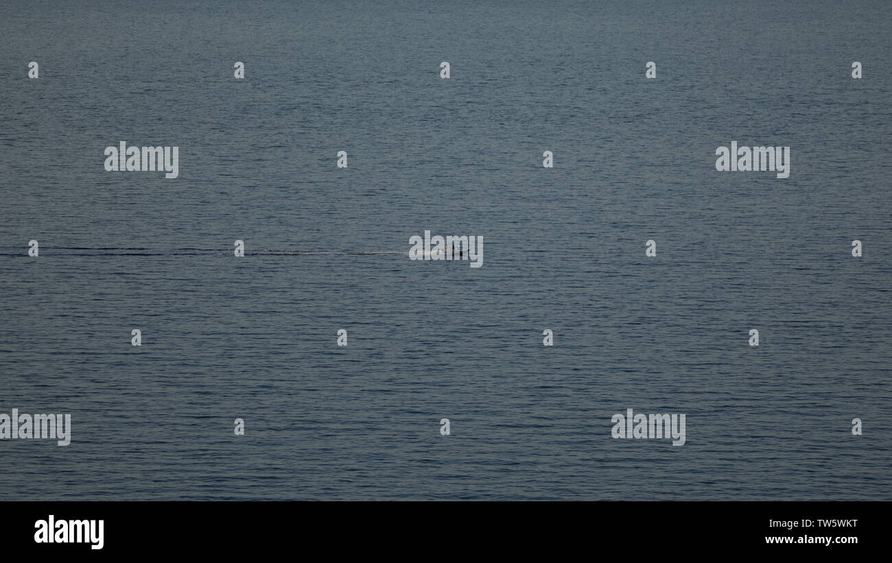 Lonely boat far away from me, small launch boat with people in the sea. Wide screen image - Stock Image