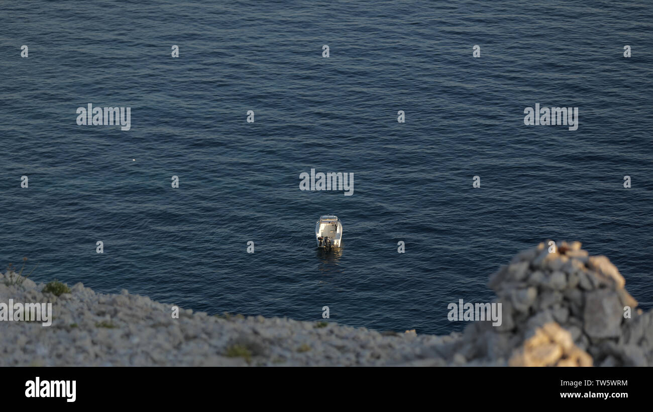 Peeping a boat from the hill. Small launch boat with people, blue sea, rocky coast - Stock Image