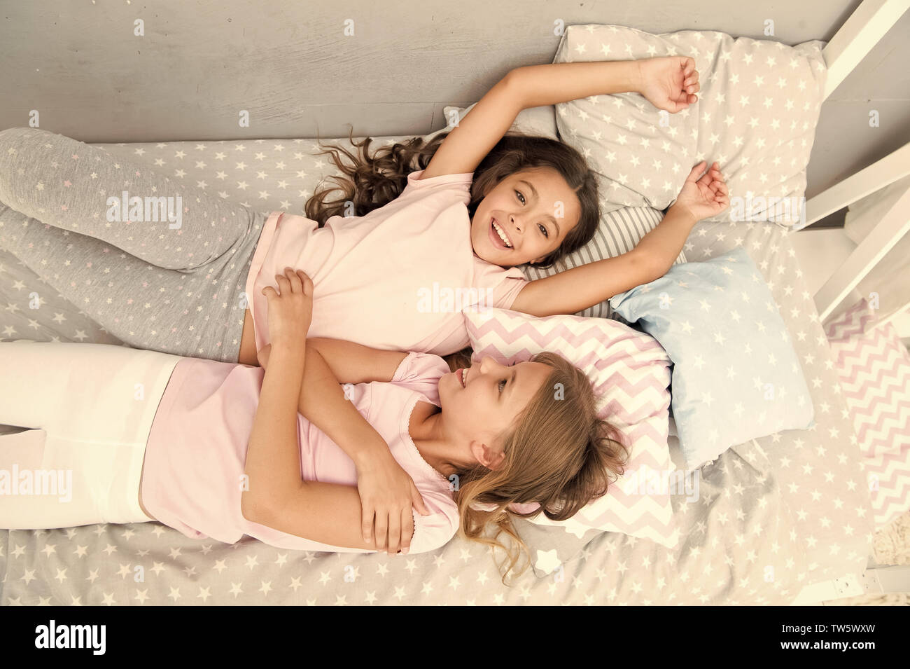 Invite friend for sleepover. Best friends forever. Consider theme slumber party. Slumber party timeless childhood tradition. Girls relaxing on bed. Sl - Stock Image