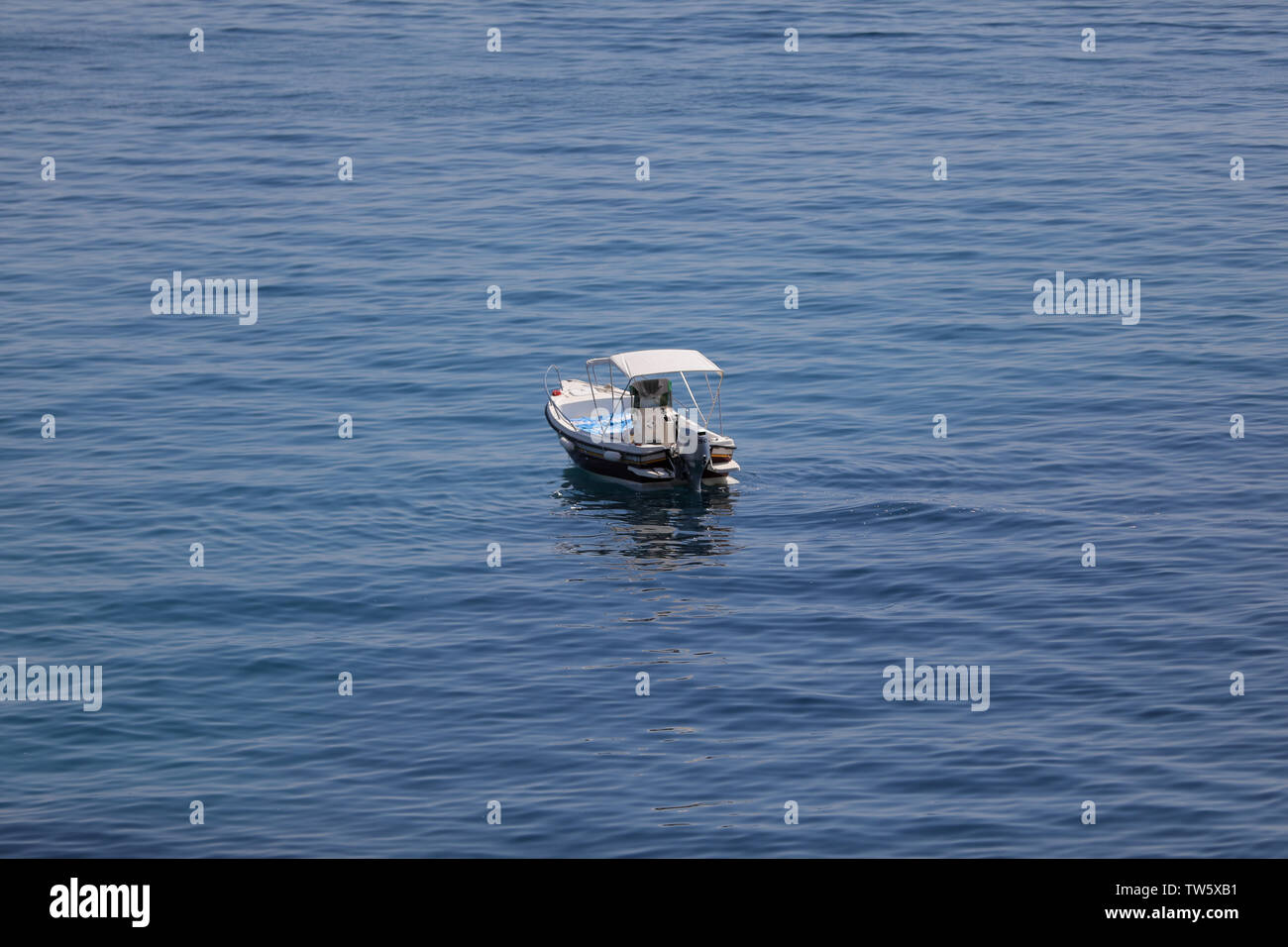 Small launch boat with people, blue sea and sky - Stock Image