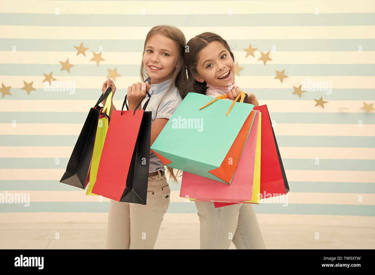 Kids happy carry bunch packages. Shopping with best friend concept. Girls like shopping. Kids happy small girls hold shopping bags. Enjoy shopping wit - Stock Image
