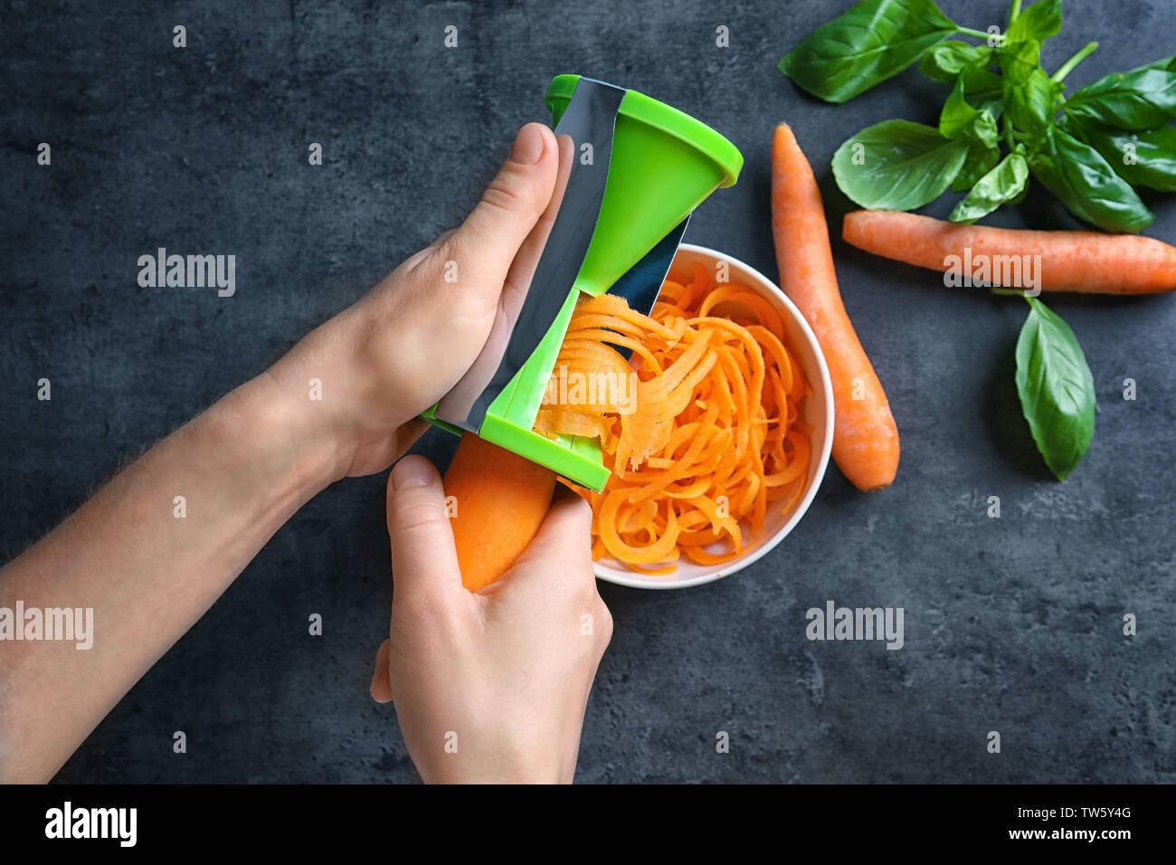 Woman using vegetable spiral slicer to make carrot spaghetti Stock Photo