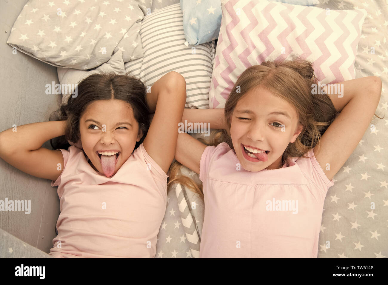 Slumber party timeless childhood tradition. Girls relaxing on bed. Slumber party concept. Girls just want to have fun. Invite friend for sleepover. Be - Stock Image
