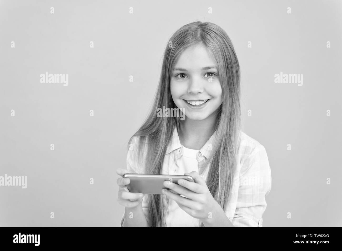Problem of youth. Mobile phone and internet addiction. Addicted to internet online games. Mobile gadget dependence. Girl small child smiling hold smartphone. Internet surfing and social networks. - Stock Image