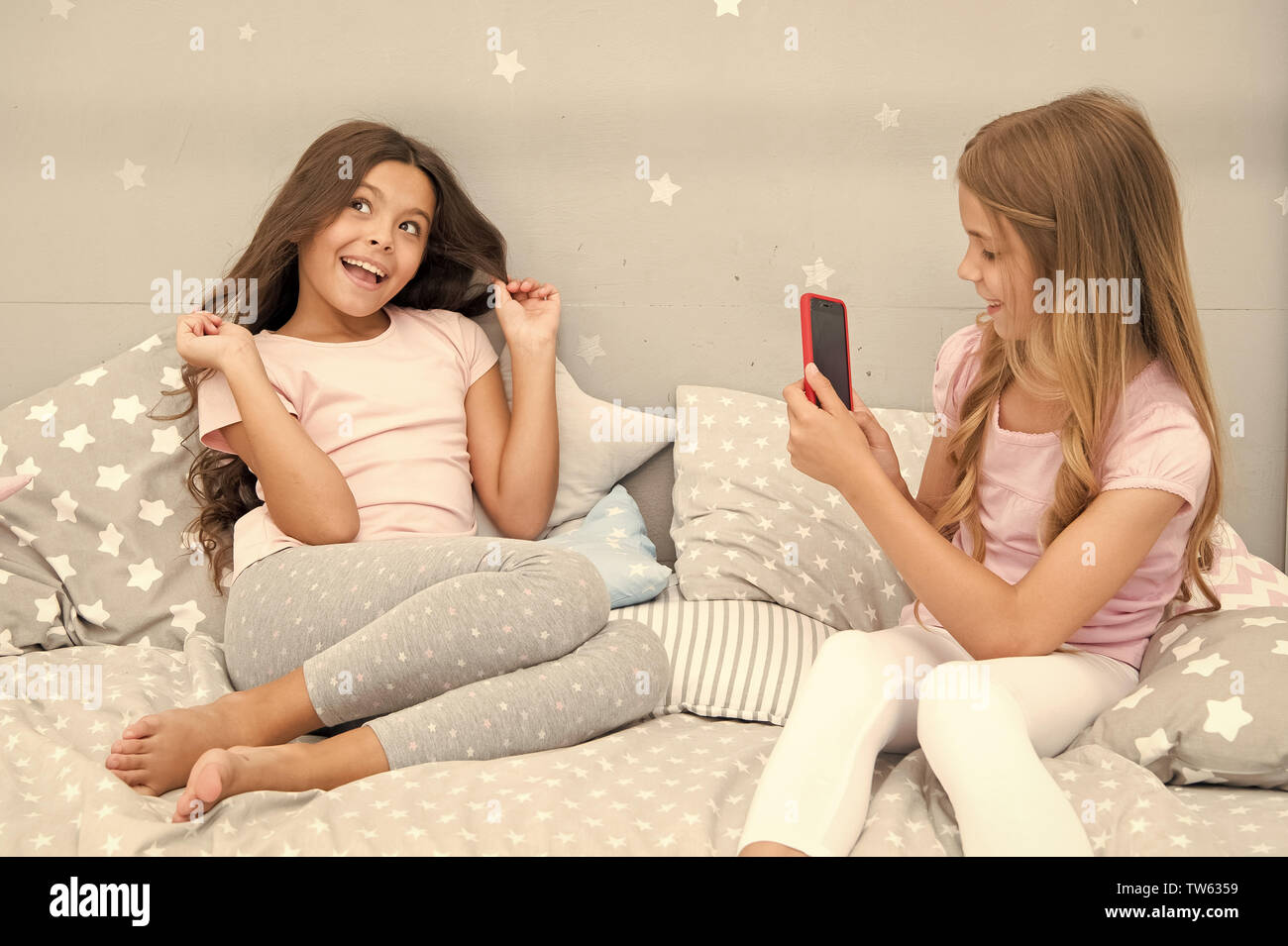Girlish leisure pajama party. Girls smartphone posing great shot. Send photo social network using smartphone. Smartphone for entertainment. Kids takin - Stock Image
