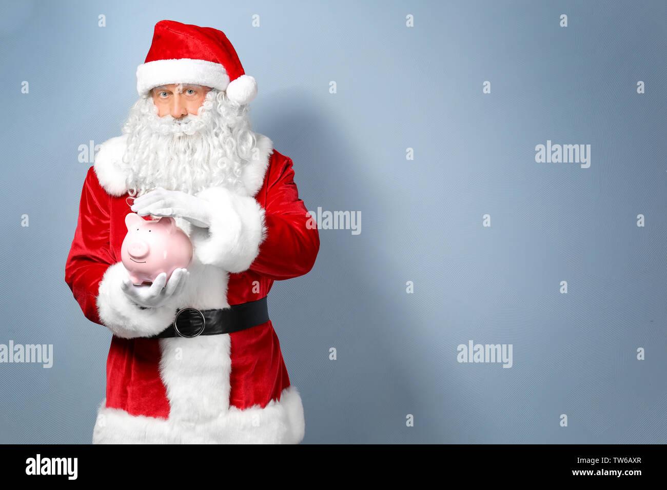 Santa Claus holding piggy bang on light background - Stock Image