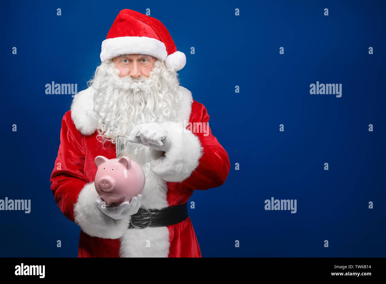 Santa Claus putting dollar into piggy bang on color background - Stock Image