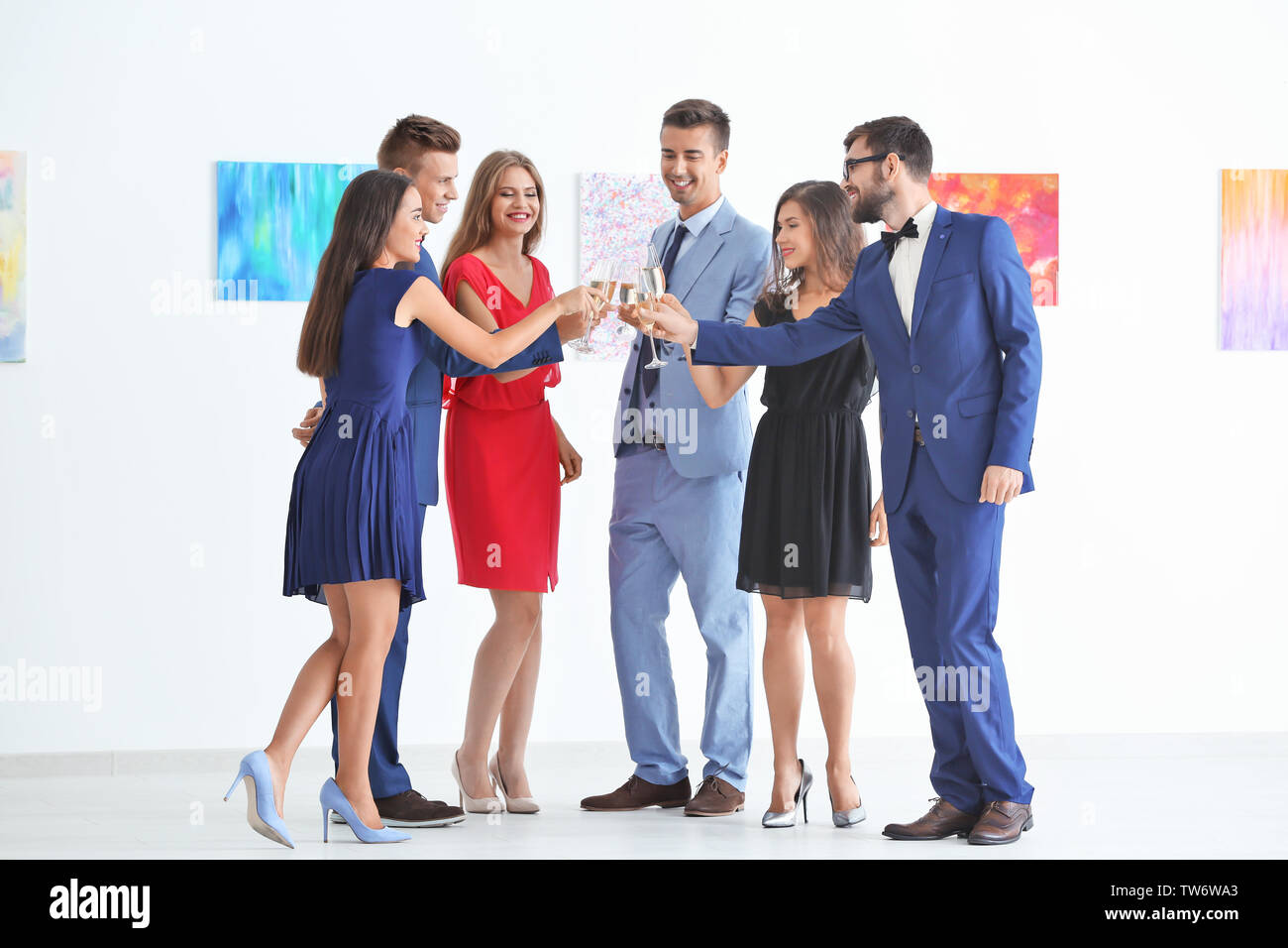 Group of people in formal wear drinking champagne at art gallery exhibition - Stock Image