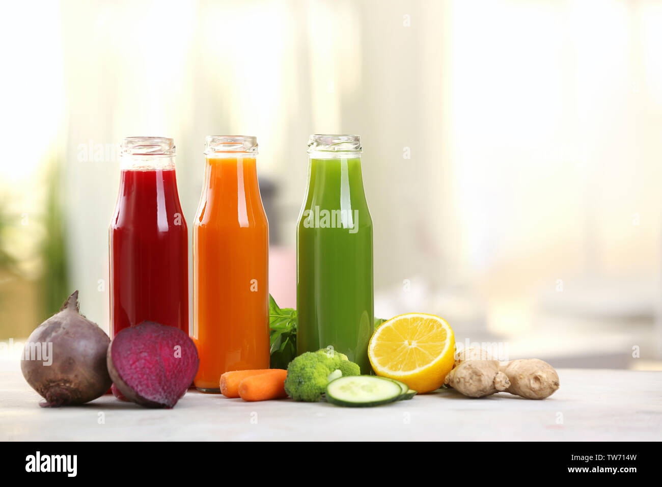 Bottles with various fresh vegetable juices on table Stock Photo