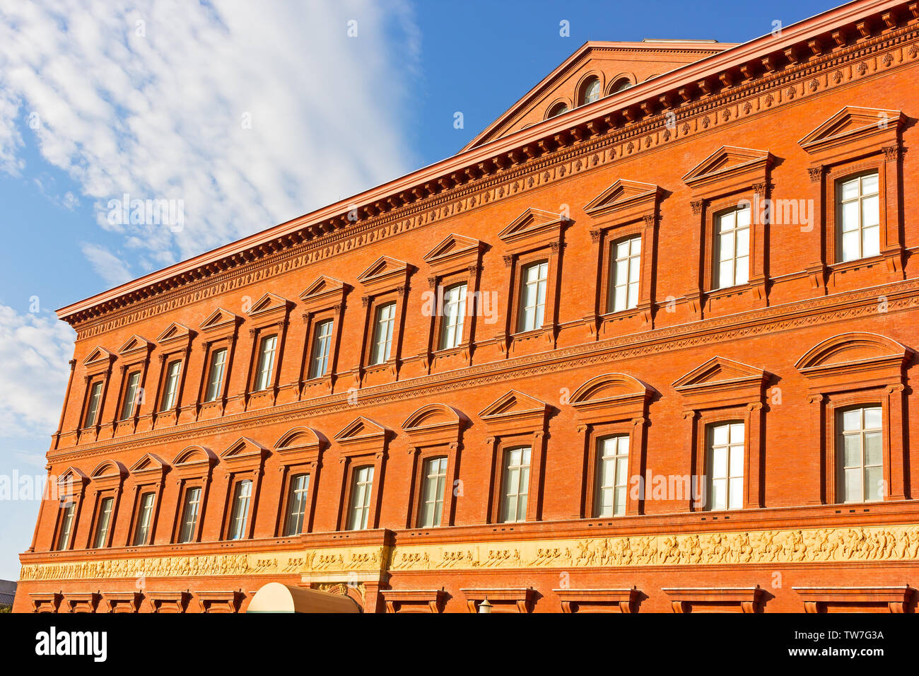 Eastern side of National Building Museum against a blue sky with clouds in Washington DC, USA. Italian Renaissance architecture of museum building in - Stock Image