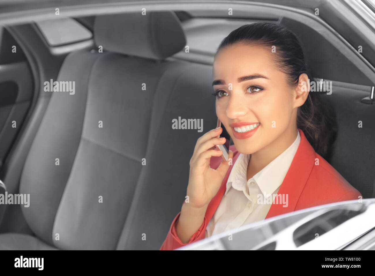 Young businesswoman on backseat of taxi car - Stock Image