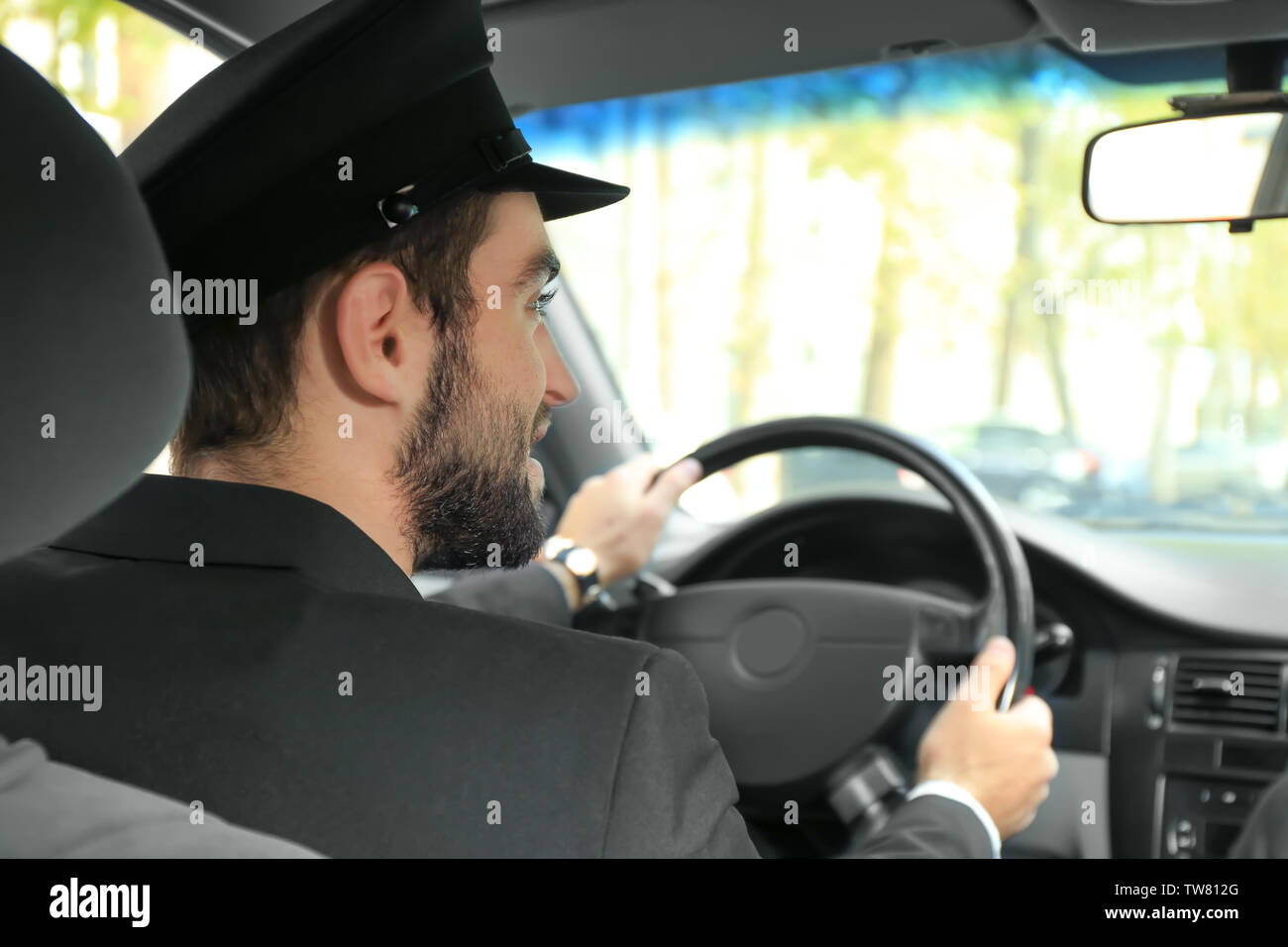Handsome man driving taxi - Stock Image