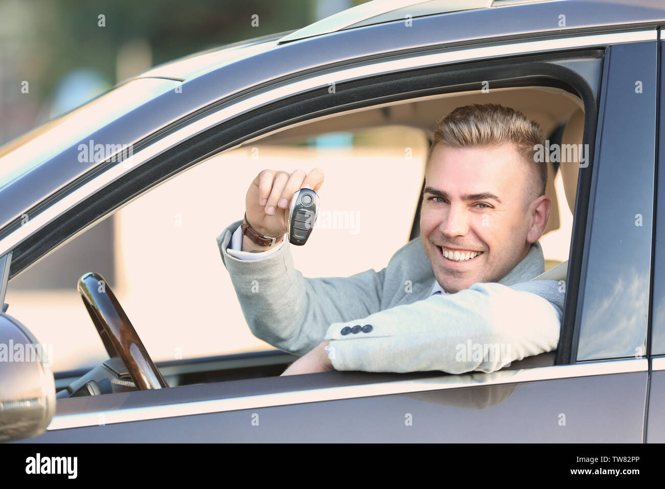 Man in formal wear holding key when sitting on driver's seat of car - Stock Image