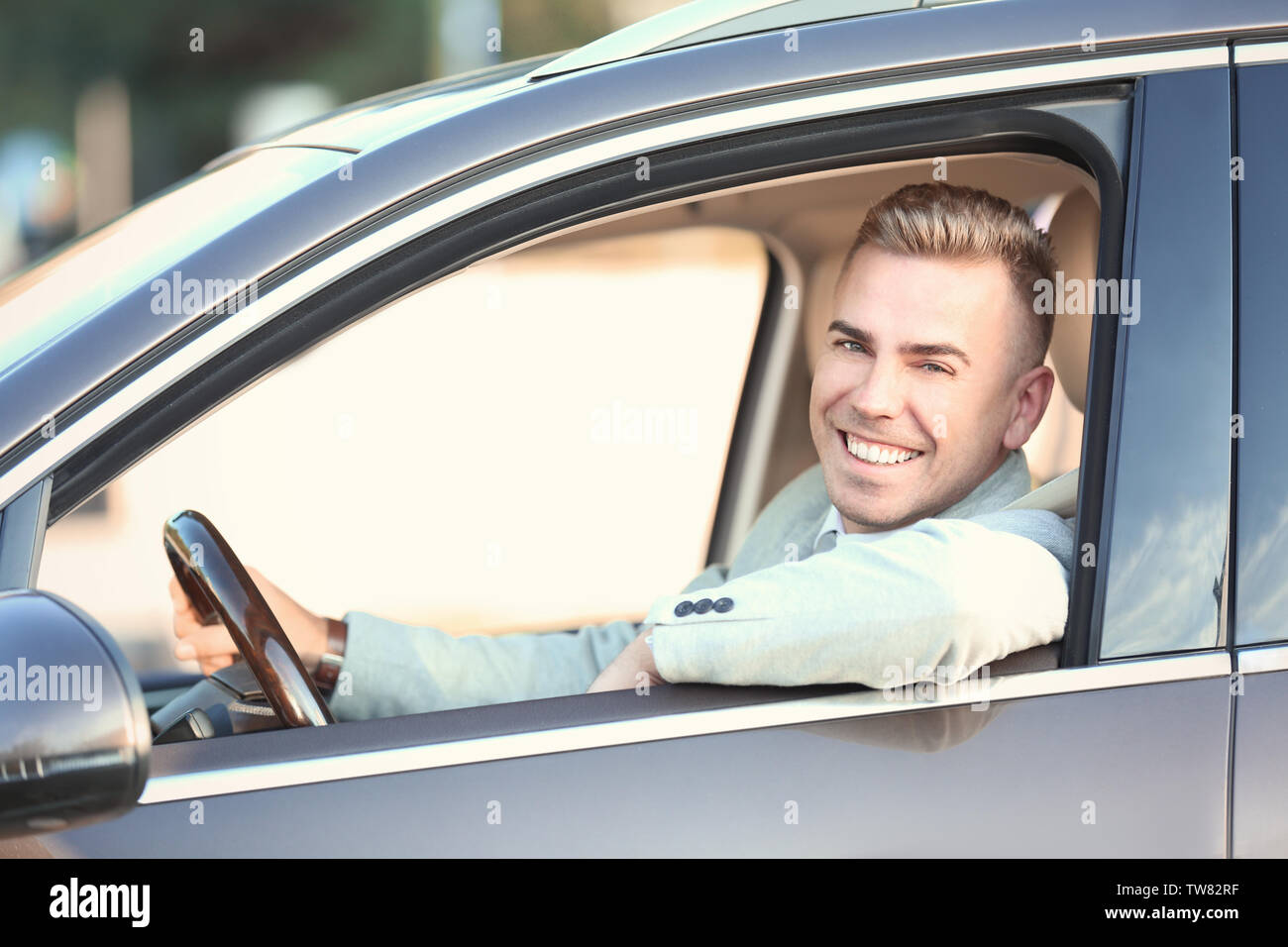 Man in formal wear on driver's seat of car - Stock Image