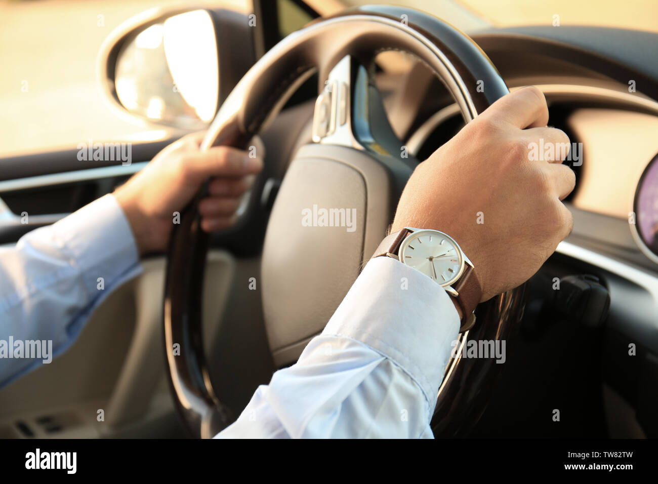 Man in formal wear driving car - Stock Image