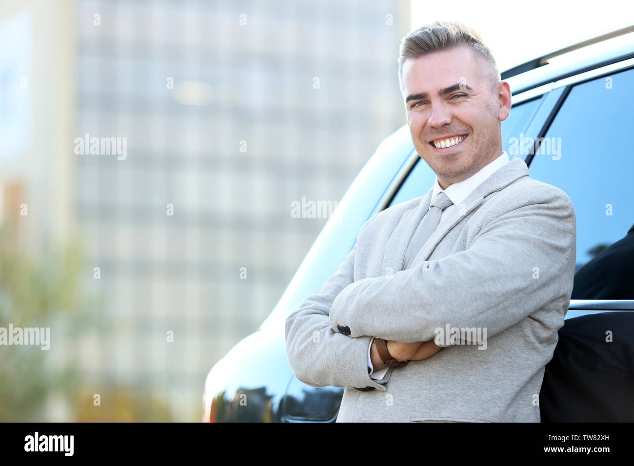 Man in formal wear standing near car on city street - Stock Image