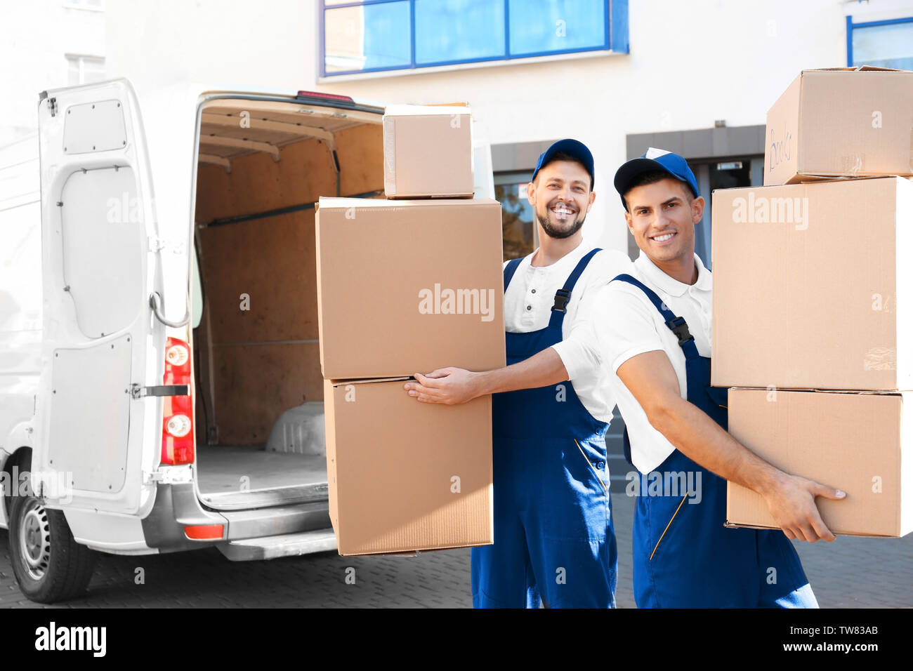 Delivery men with moving boxes near car - Stock Image