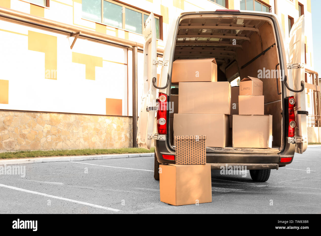Open car trunk with moving boxes outdoors - Stock Image