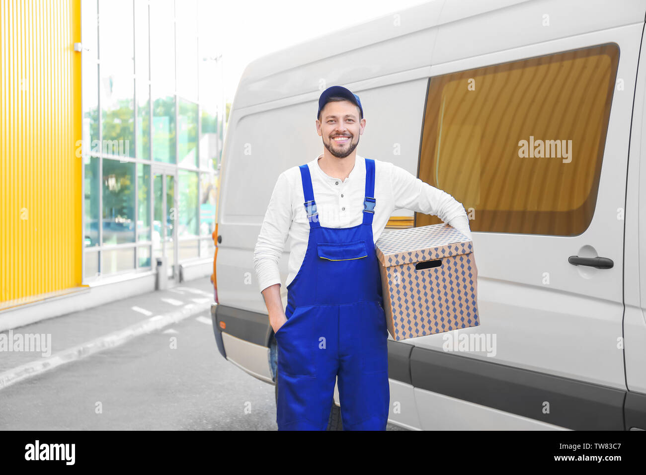 Delivery man with moving box near car - Stock Image