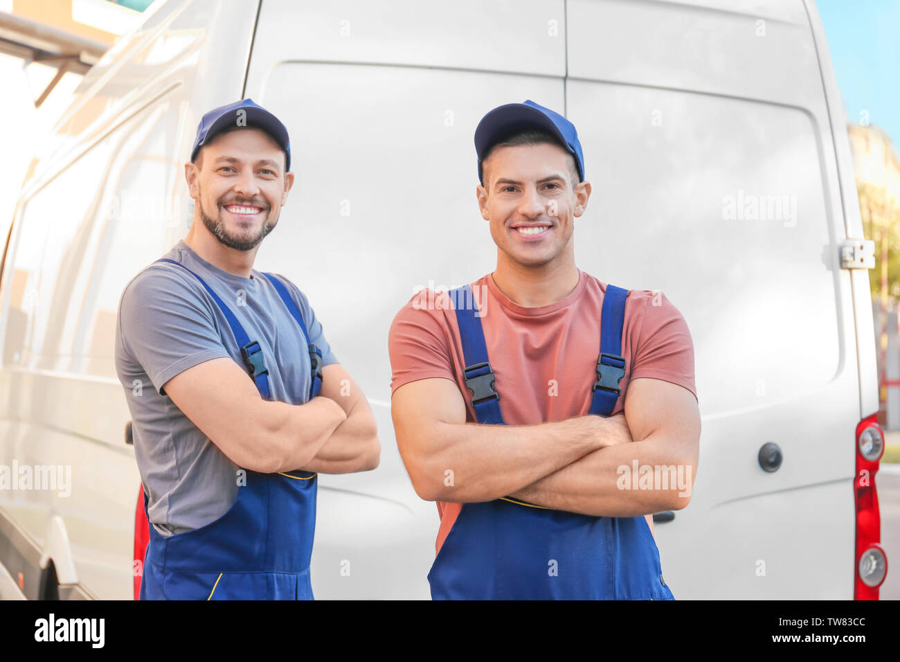 Delivery men standing near car - Stock Image