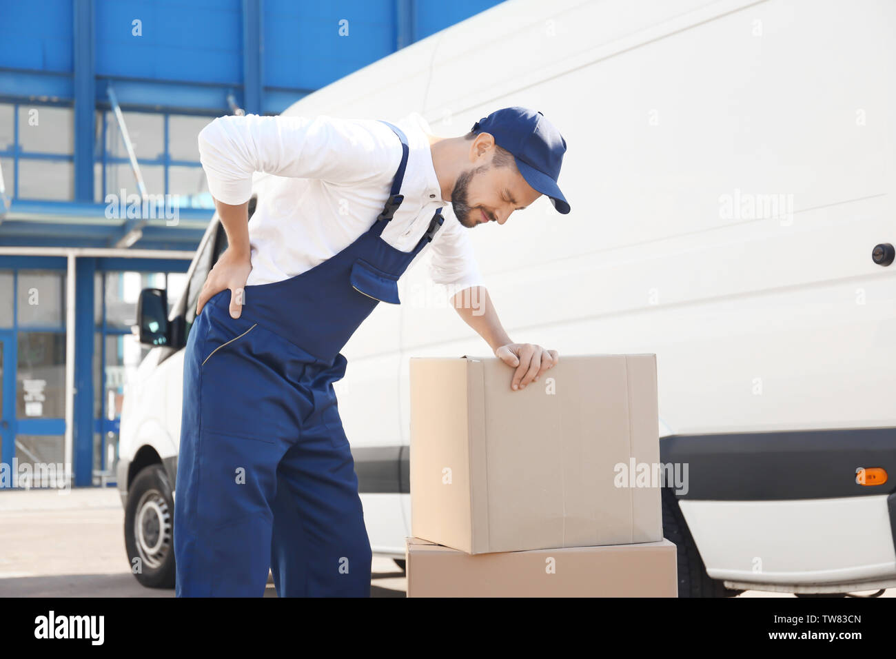 Delivery man suffering from pain after moving heavy box near car - Stock Image