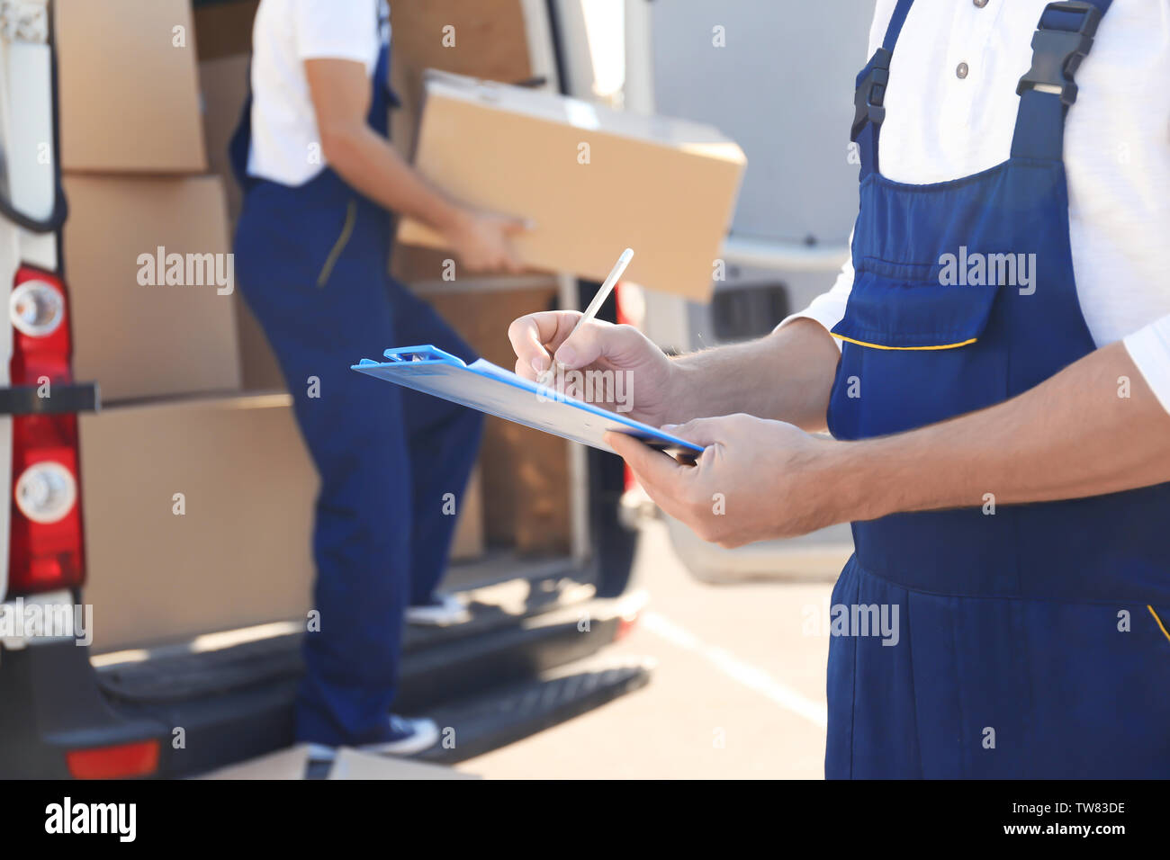 Delivery man checking list on clipboard near car - Stock Image