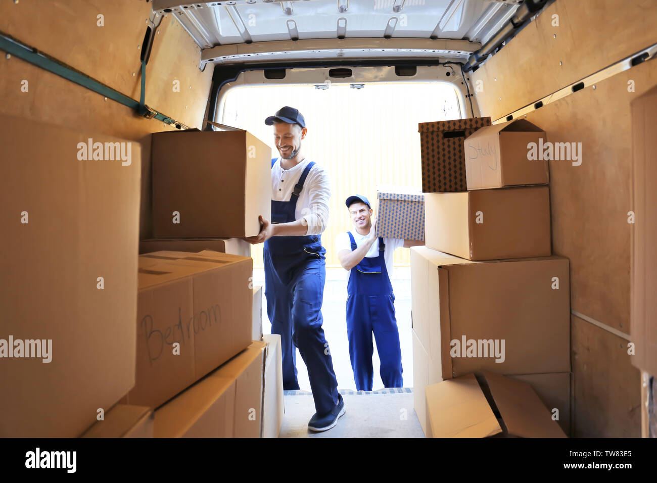 Delivery men unloading moving boxes from car - Stock Image