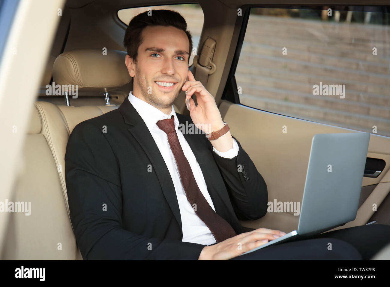 Man in formal wear with laptop talking on phone in car - Stock Image