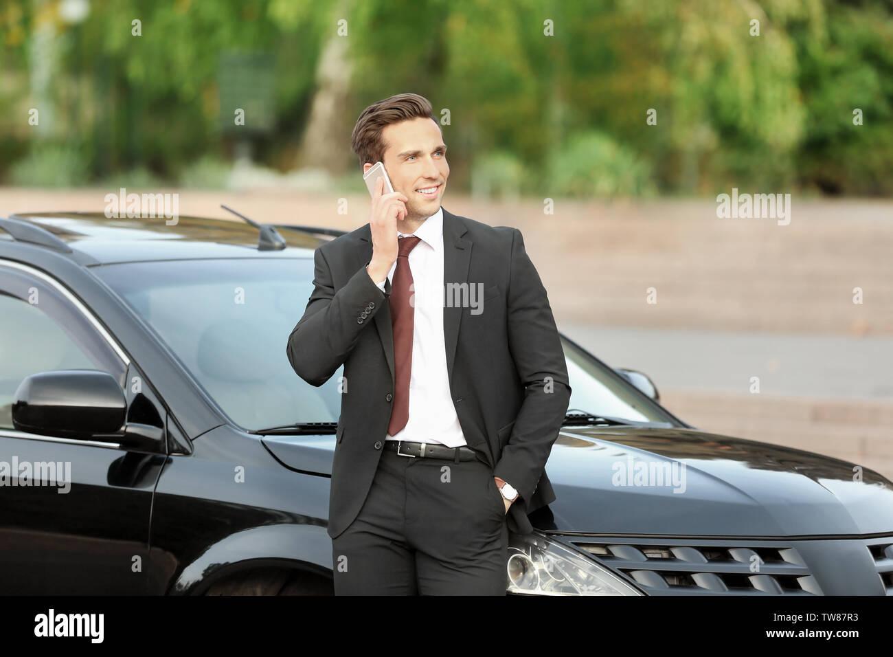 Man in formal wear talking on phone near car outdoors - Stock Image