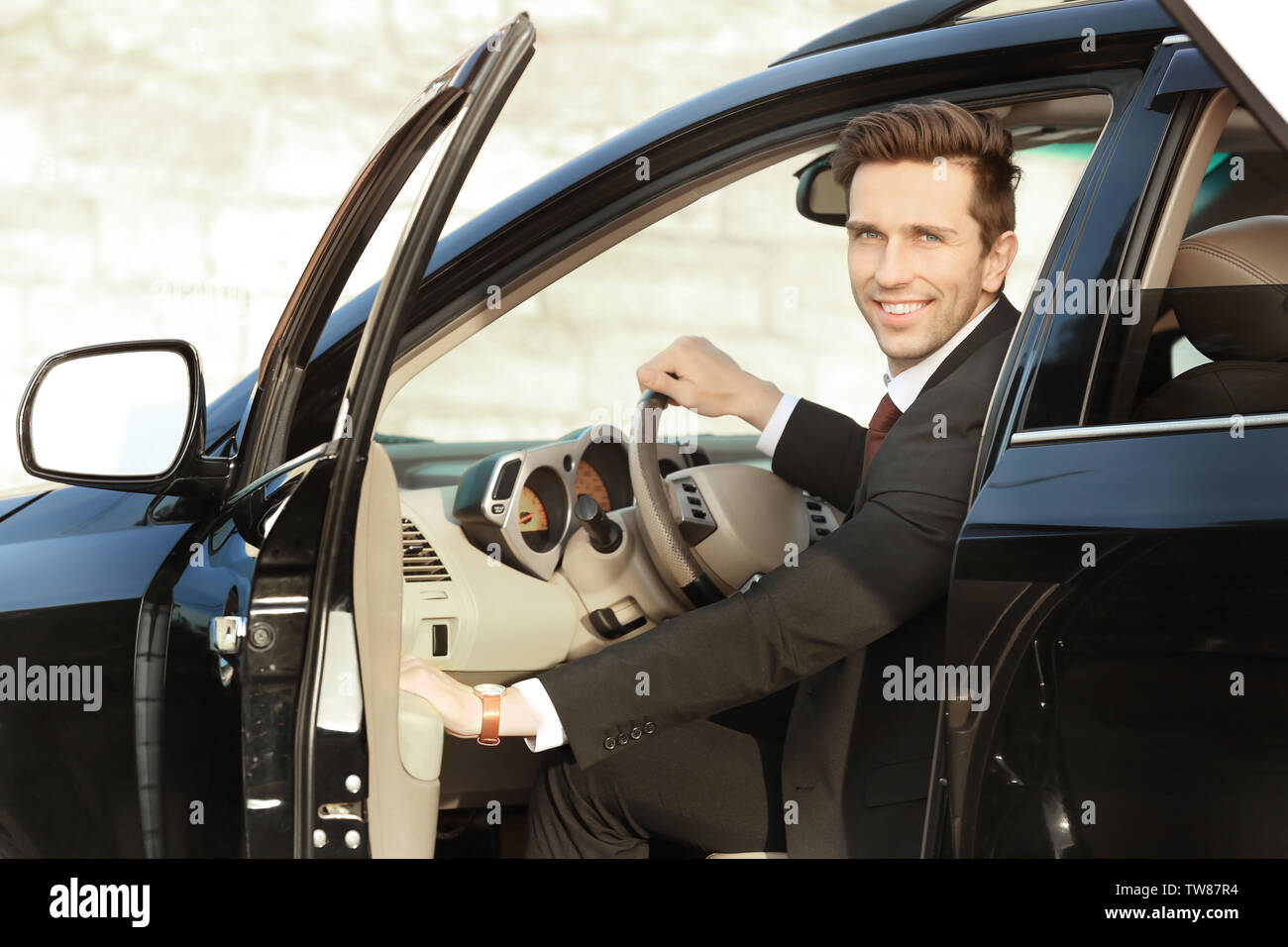 Man in formal wear getting out of car - Stock Image