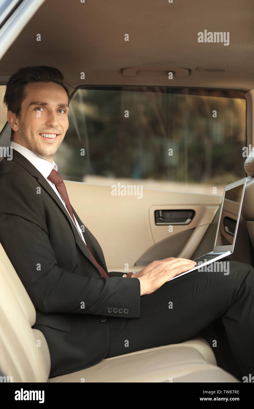 Man in formal wear with laptop in car - Stock Image