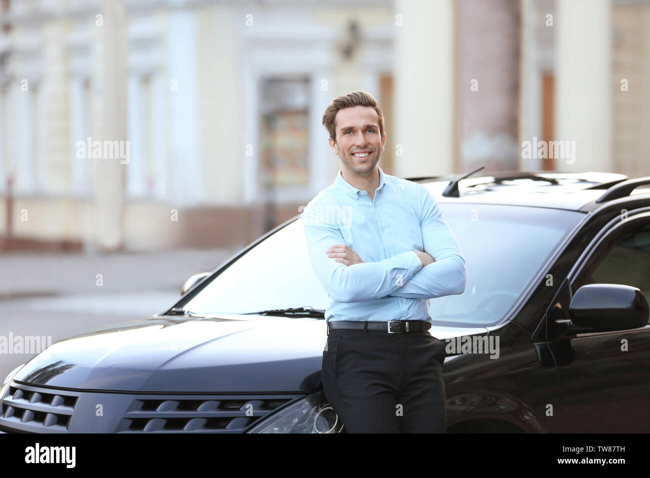 Man in formal wear standing near car outdoors - Stock Image