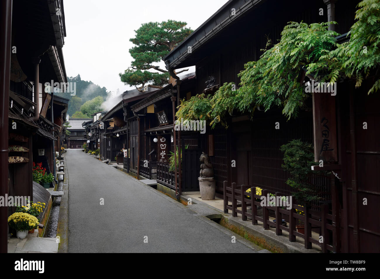 Kamisannomachi, old town street of Takayama city in early morning with steam coming from a sake brewery shop. Kamisannomachi is a merchant town street - Stock Image