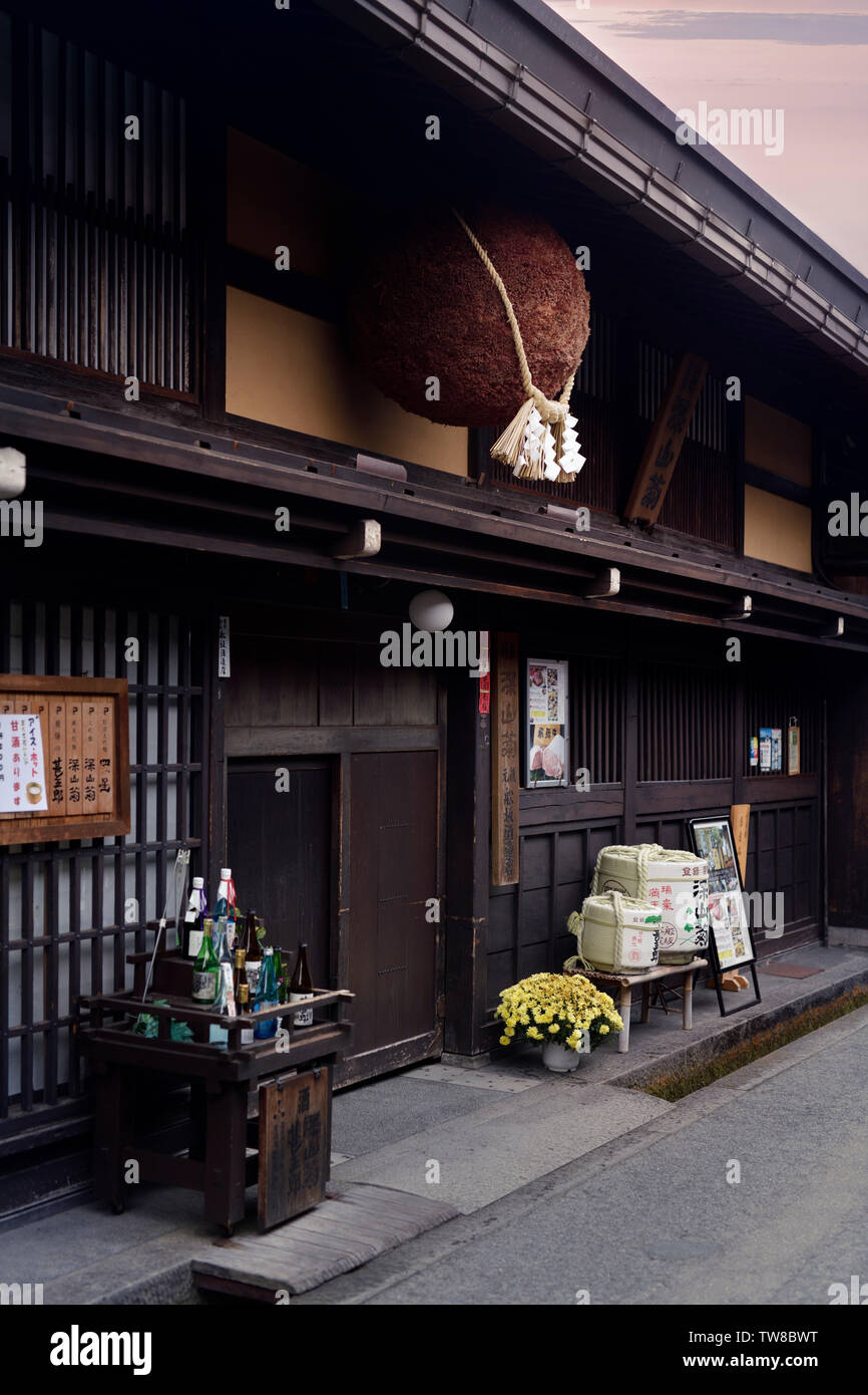 Sugidama, brown cedar ball, hanging above the entrance of a sake brewery in Takayama, on the old town Kamisannomachi street. The cedar orb hanging out - Stock Image