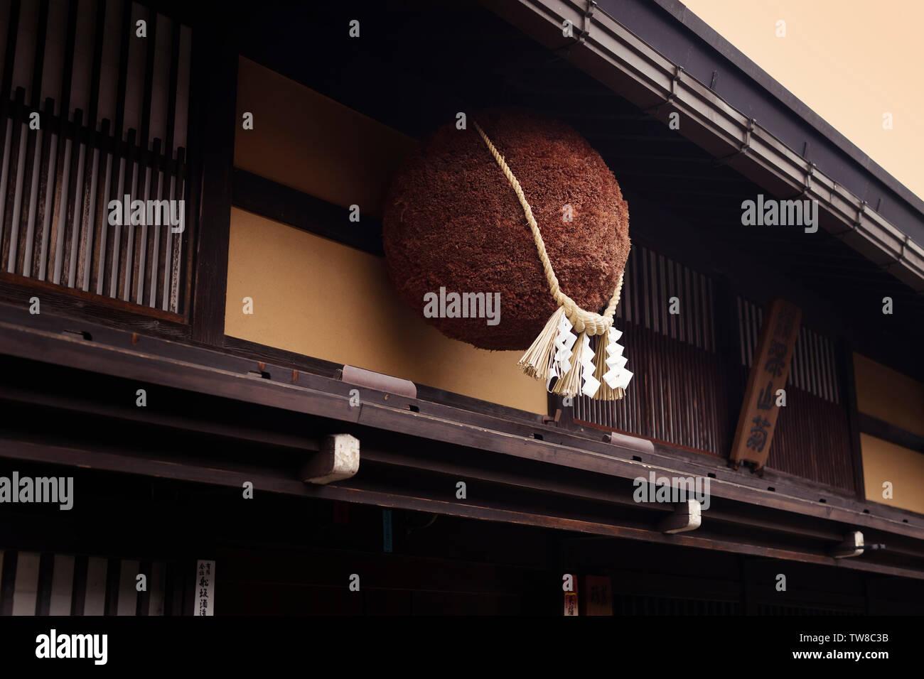 Sugidama, brown cedar ball, or orb, with Shinto Shimenawa rope tied around it, hanging above the entrance of a sake brewery in Takayama, Gifu, Japan - Stock Image