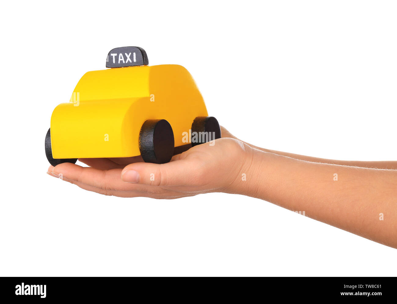 Woman holding yellow toy taxi cab on white background - Stock Image