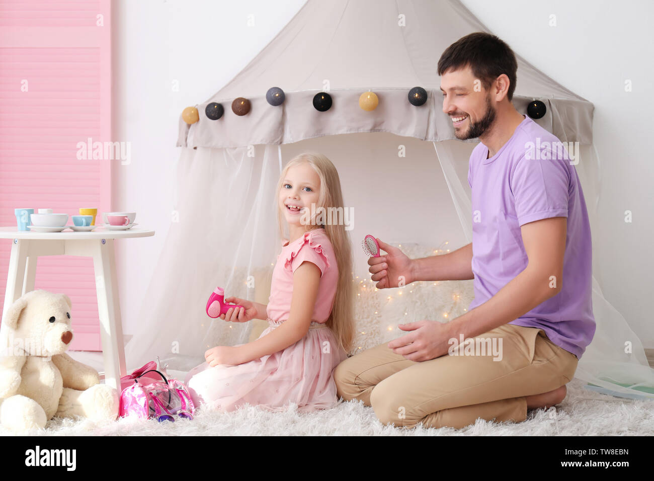 Father brushing hair oh his little daughter at home - Stock Image