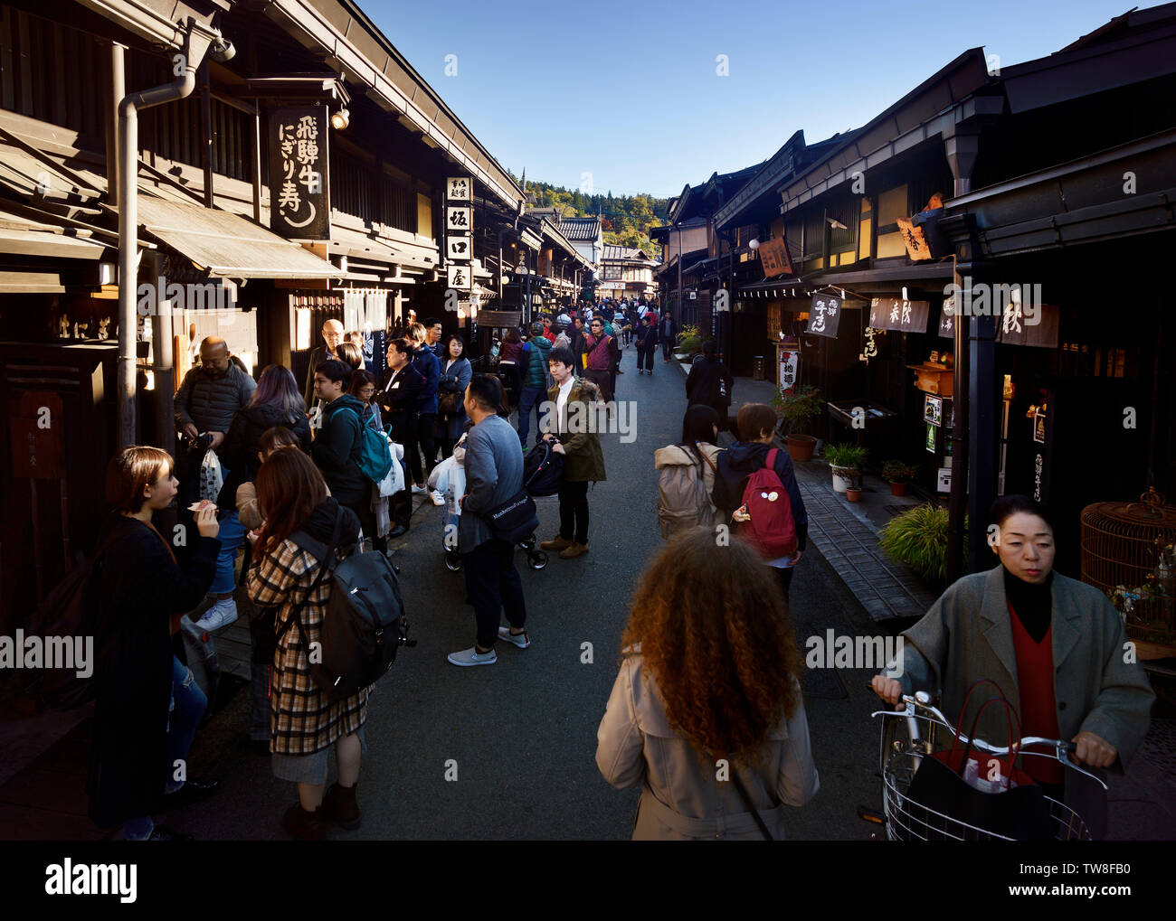 Kami-Sannomachi, old town market street of Takayama city busy with tourists. Kamisannomachi is a merchant town street lined with shops and restaurants - Stock Image