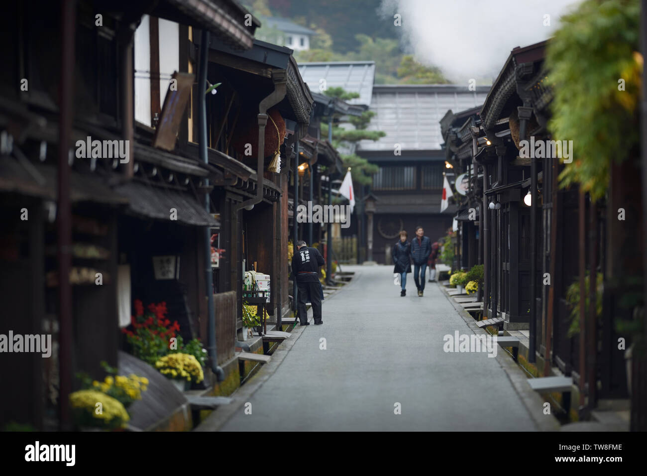 Morning scenery of Kamisannomachi, old town merchant street in Takayama city. Sake brewery owner is cleaning his shop and a couple walking - Stock Image