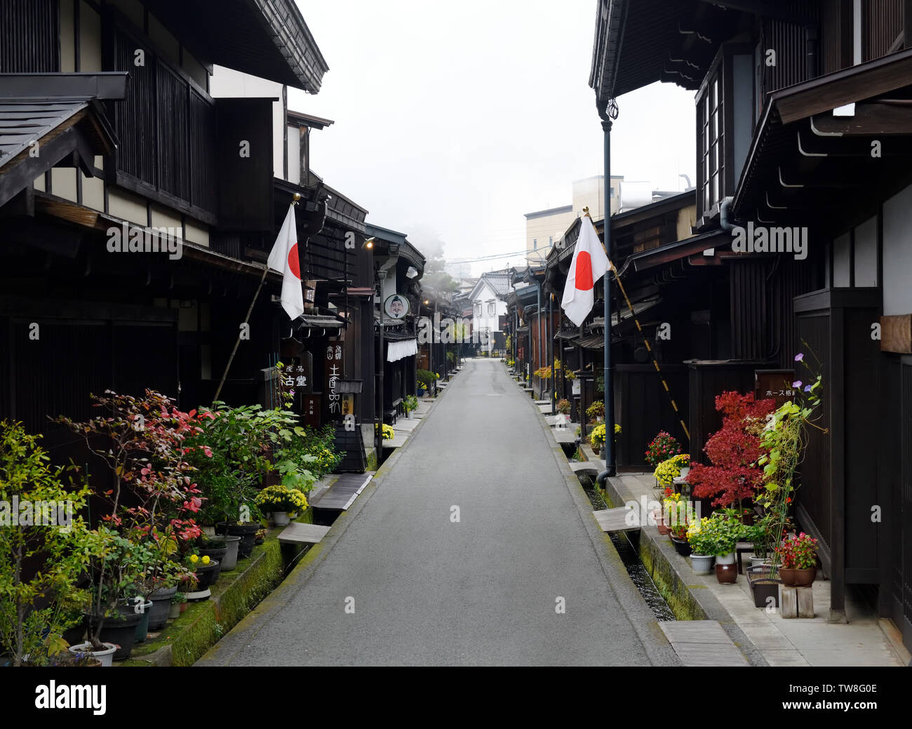 Morning scenery of Kamisannomachi, old town street in Takayama city with Japanese flags outside on a Culture day public holiday in Japan. Kami-sannoma - Stock Image